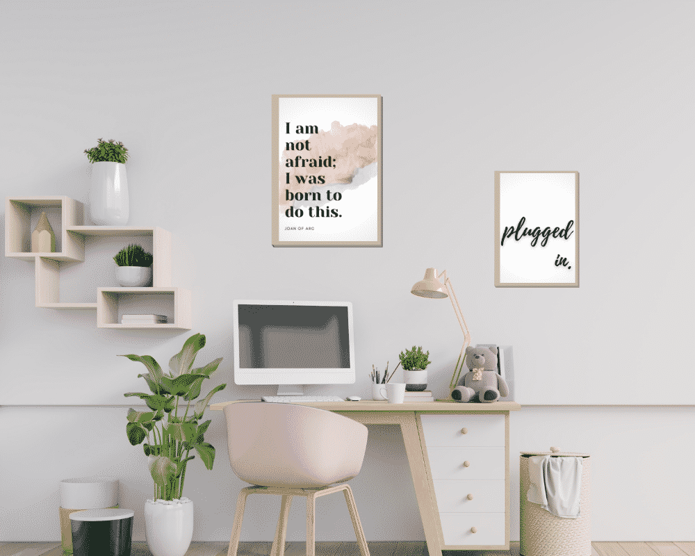 Desk with a plant, pink decorations, and motivational quote art to help you stay positive.