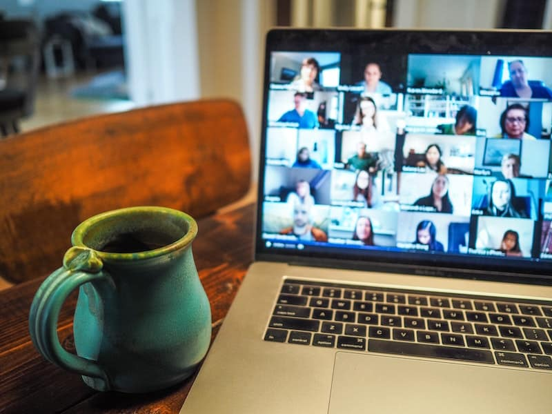 Laptop displaying a zoom call sits on a desk next to a mug.