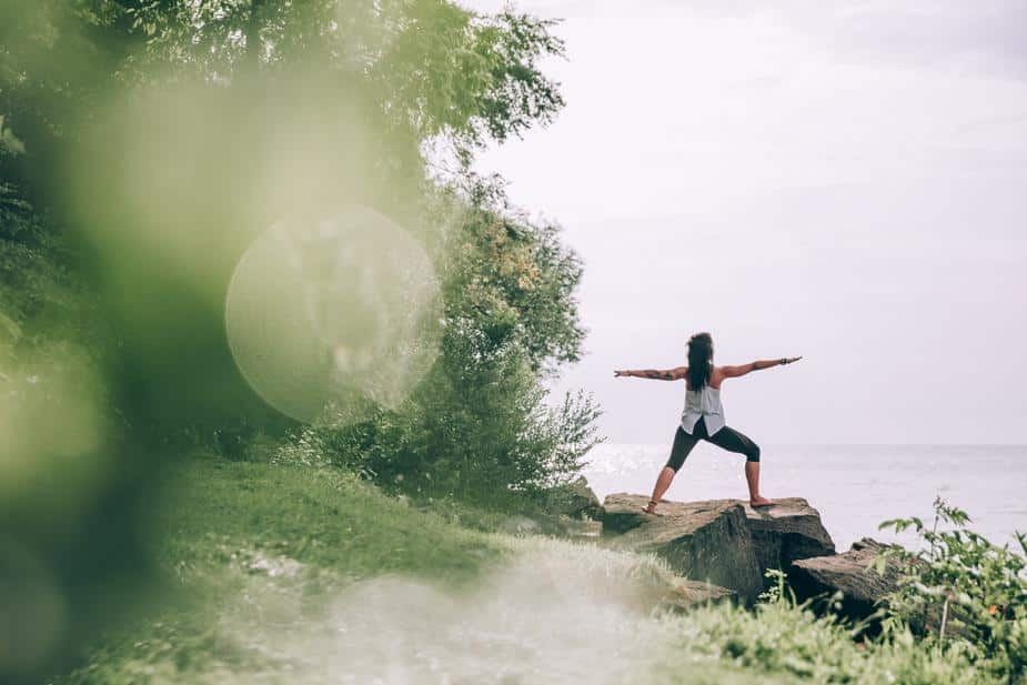 A woman does yoga on a path by the water