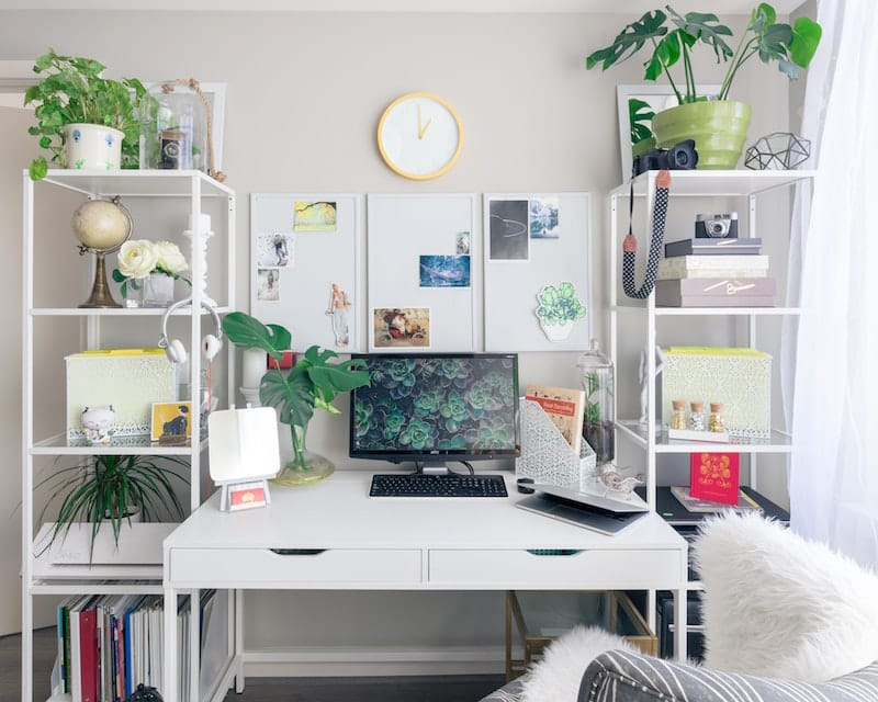 A white desk is bathed in sunlight, decorated with green plants and fun personal items to help you stay positive.