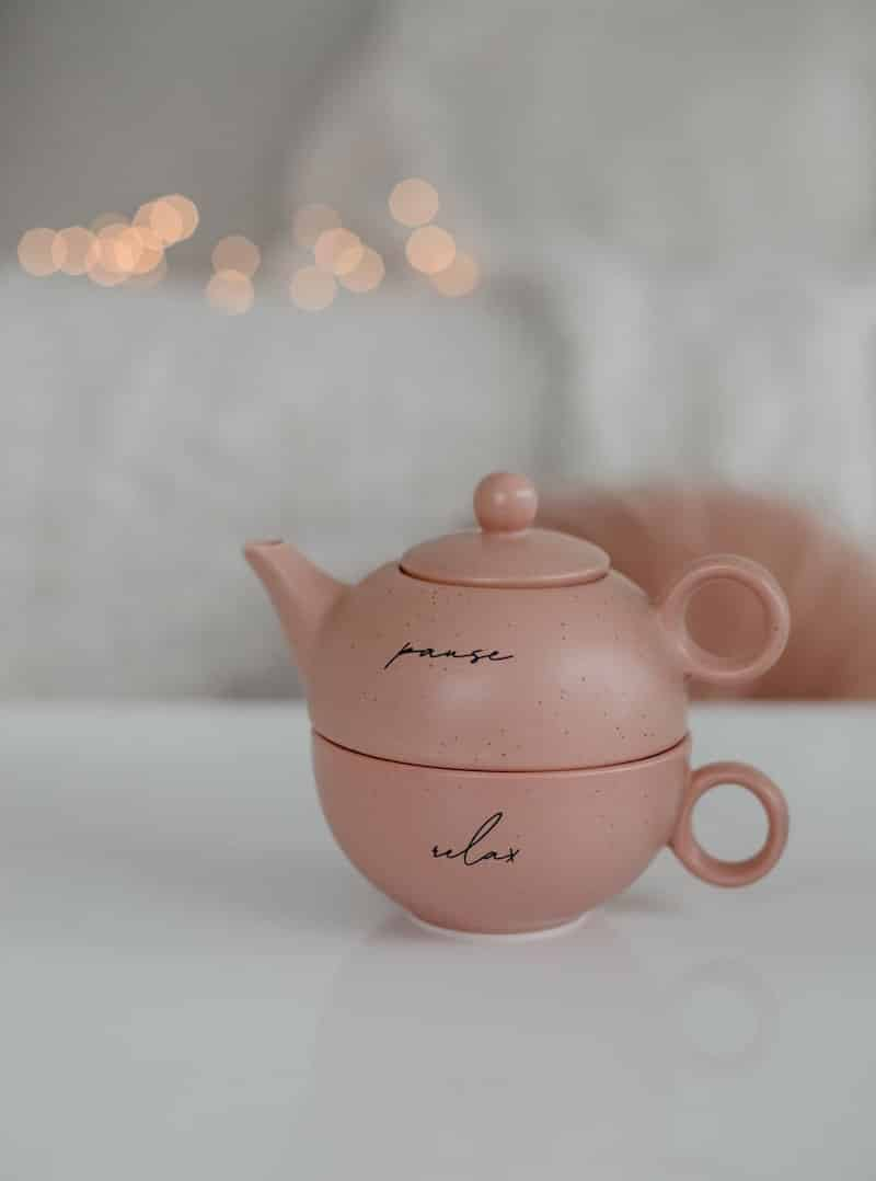 """A pink teapot with the words, """"pause"""" and """"relax"""" sits on a table"""