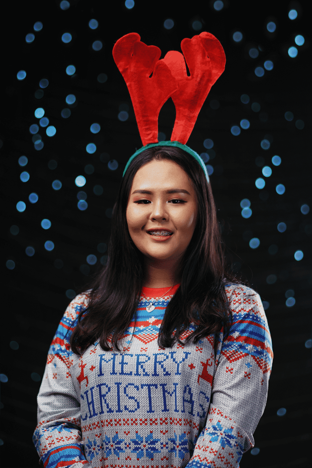An employee wears an ugly Christmas Sweater with reindeer antlers for a virtual office holiday party