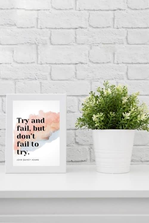 Framed motivational quote art on a desk