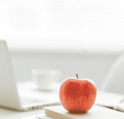 An apple sits on a desk