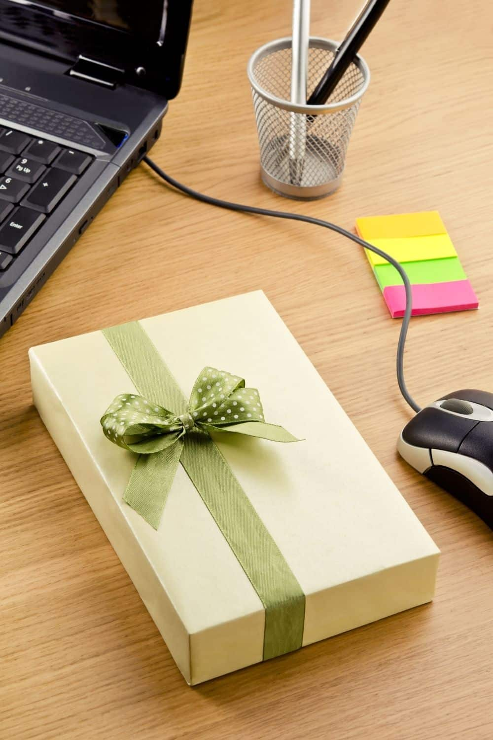 A gift sits on a desk next to a laptop