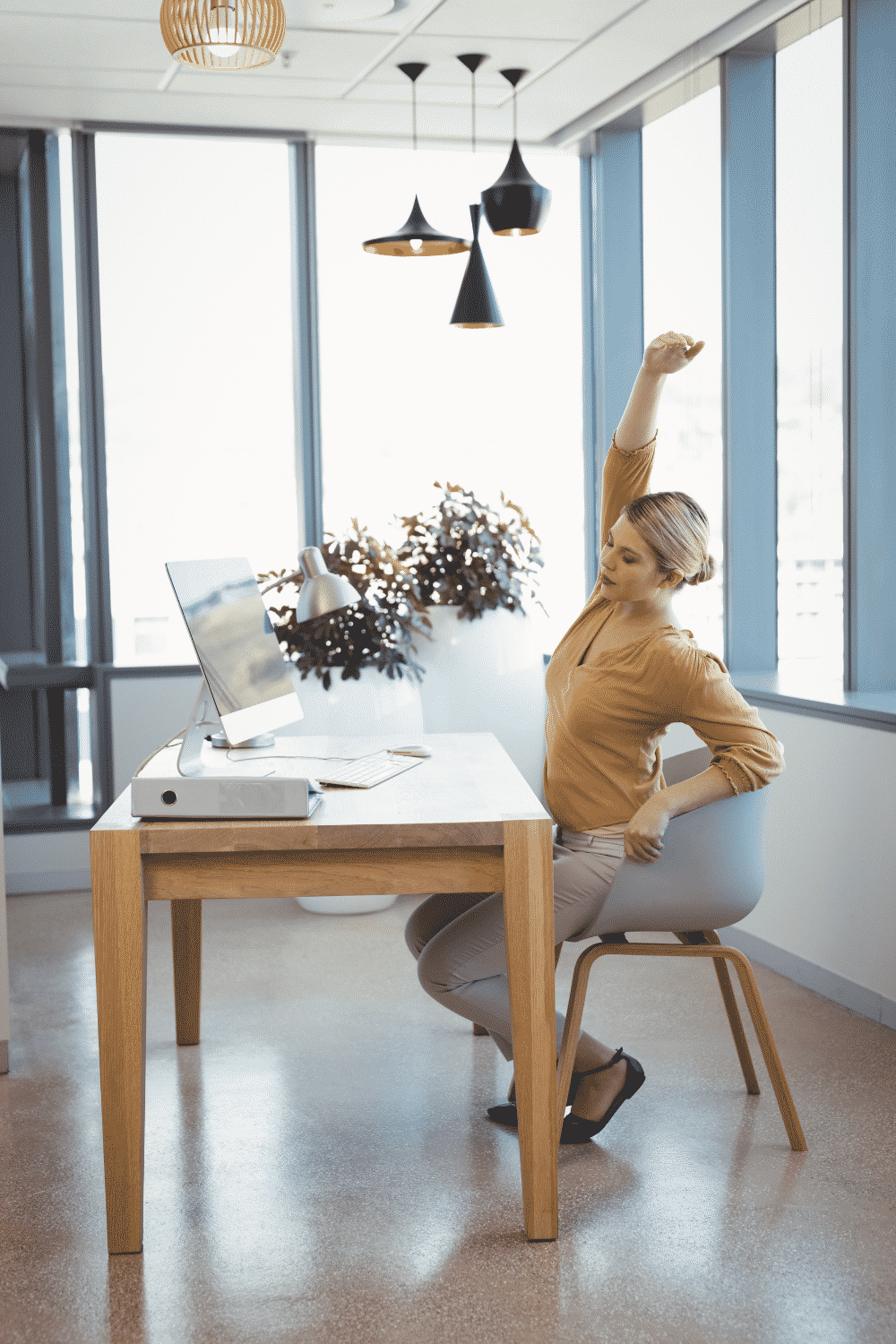 A woman stretches while working from home