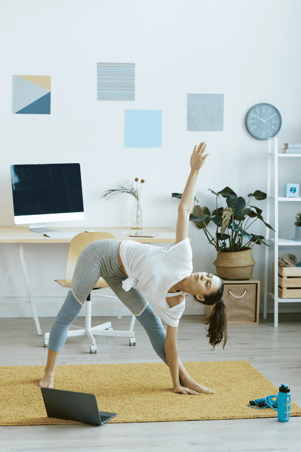 A woman does yoga in her home office