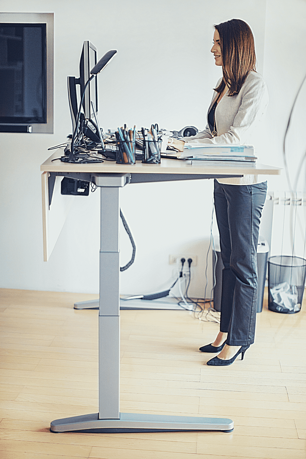 A woman stands in front of a computer at a standing desk