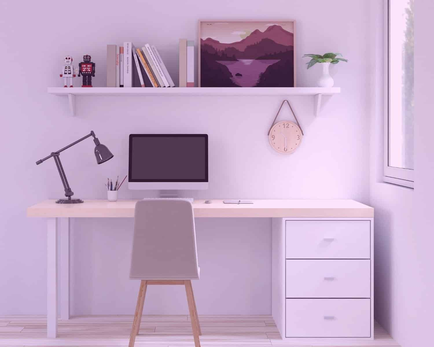 An empty desk sits bathed in light with a painting sitting on a shelf above