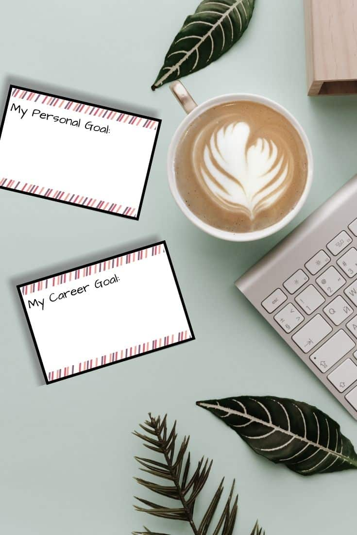 Goal cards lay on a desk next to a cup of coffee and a keyboard