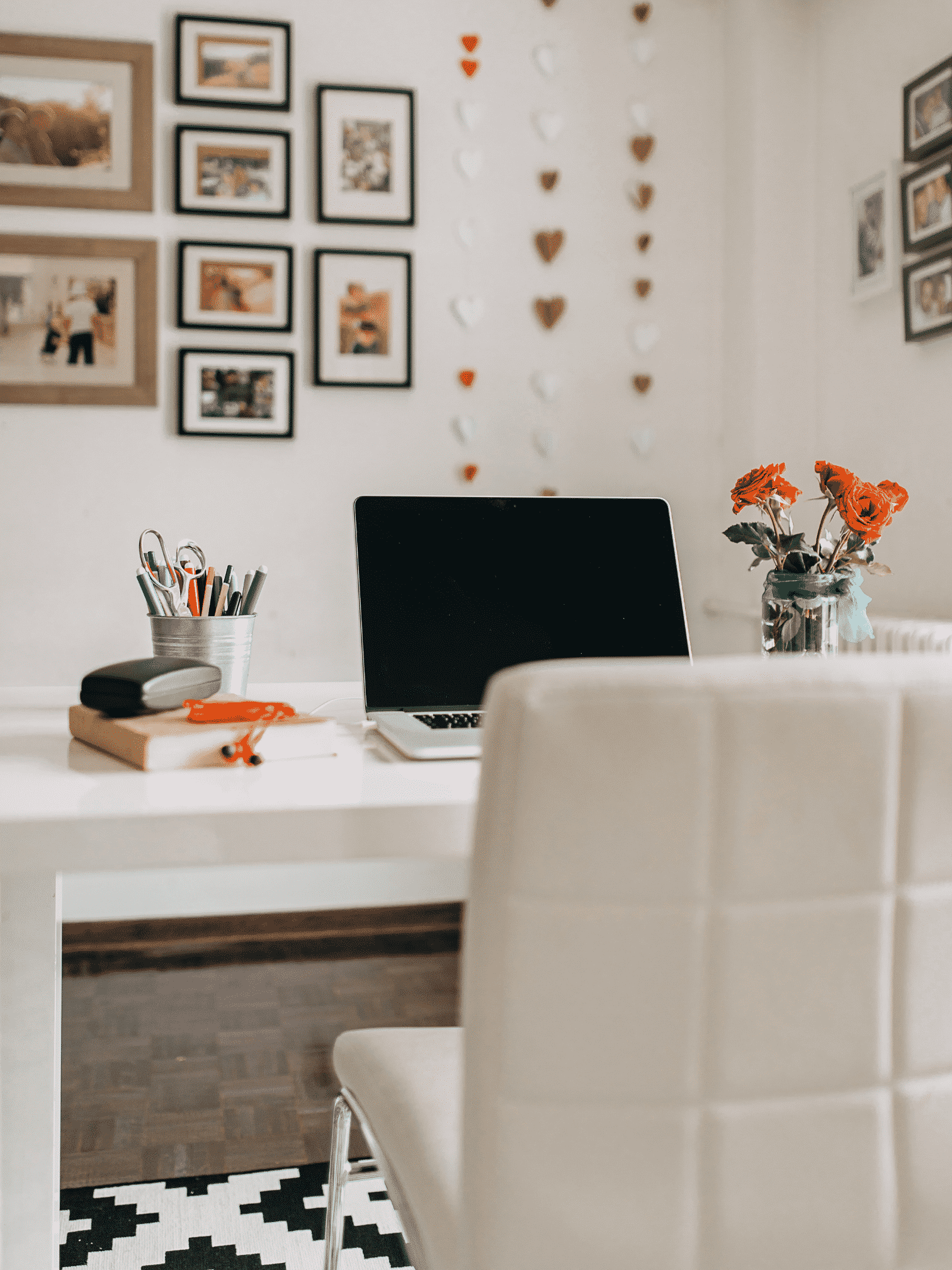 Desk at a home office with a plant and photos on the wall