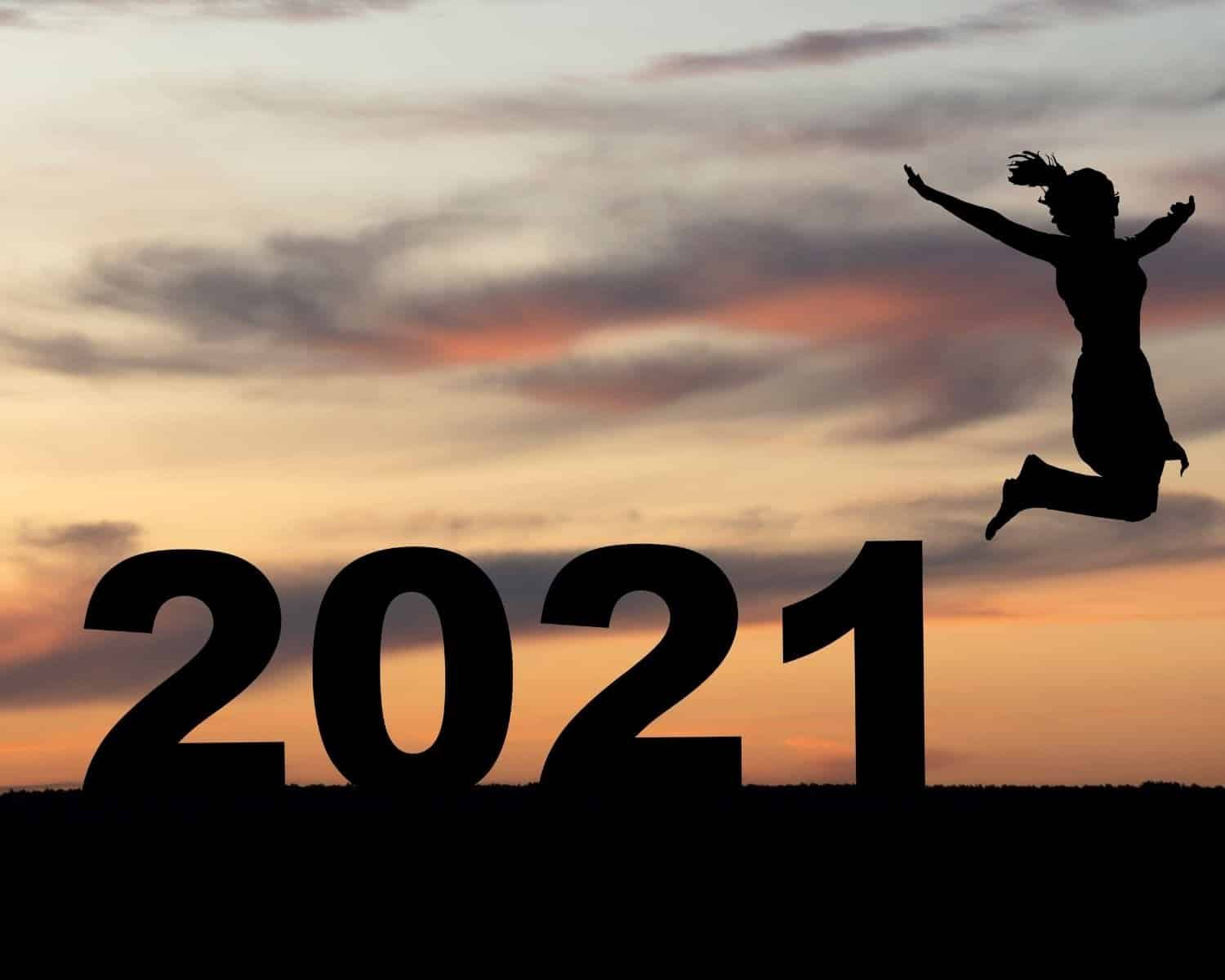 A woman jumps in the air in front of a 2021 sign