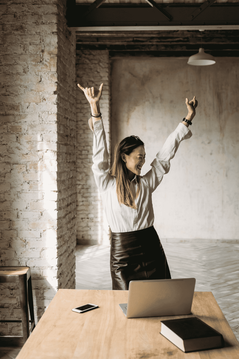 A woman stands with her hands in the air as if dancing while her computer sits on the table in front of her