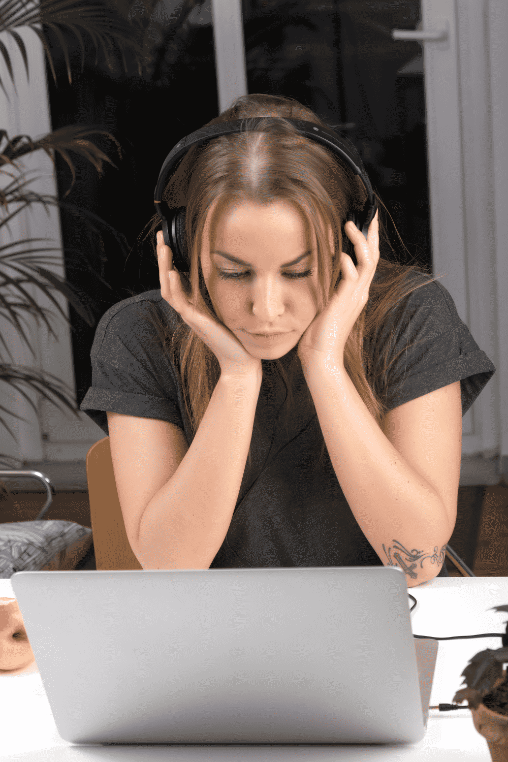 A woman listens to music through headphones while looking at her computer