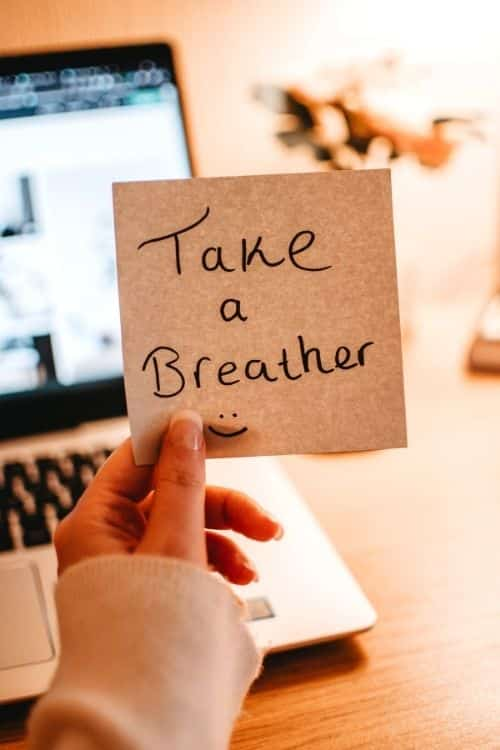 "A woman holds a post-it that says ""Take a Breather"" in front of her computer"