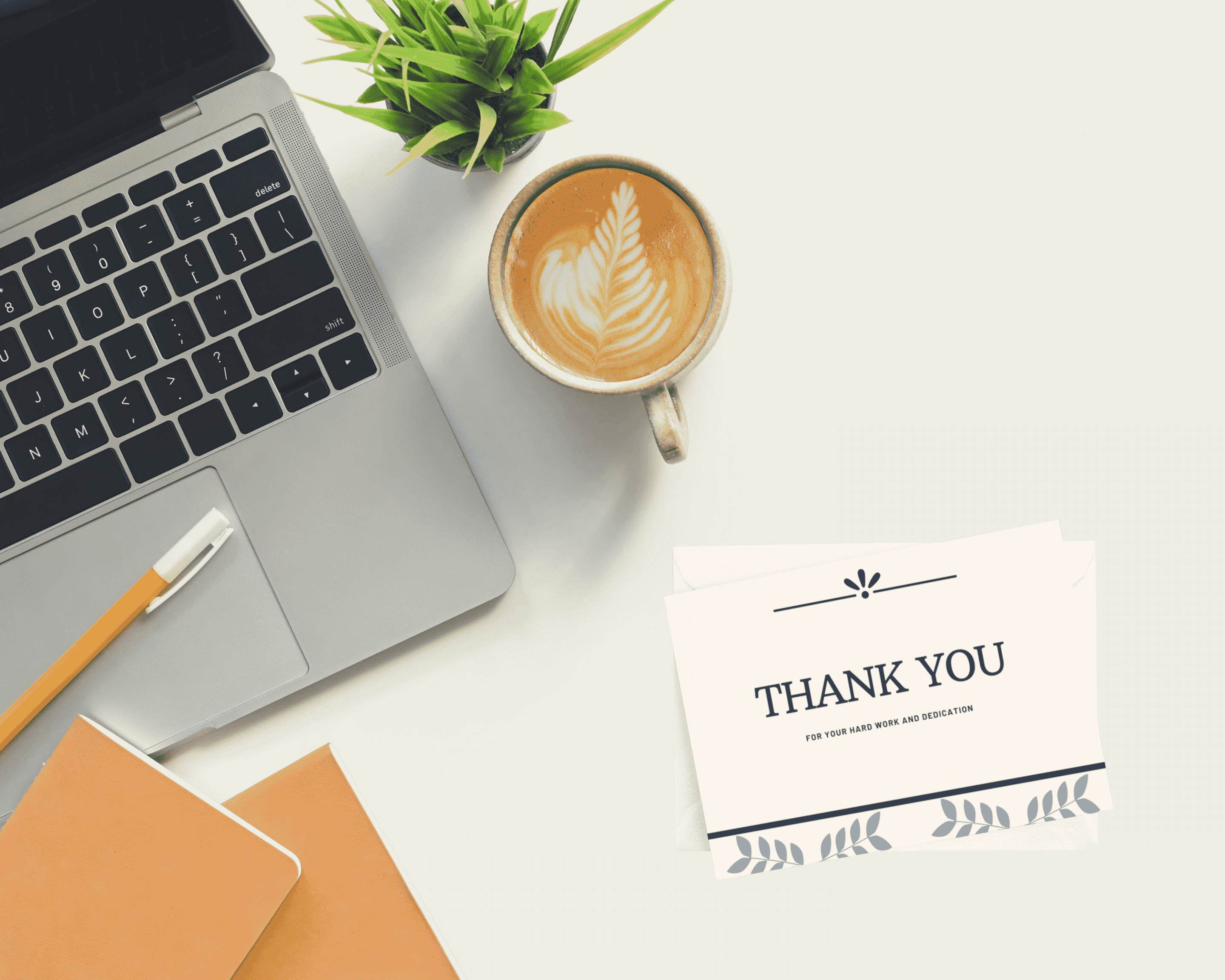 A thank you card sits on a desk next to a laptop and mug of coffee