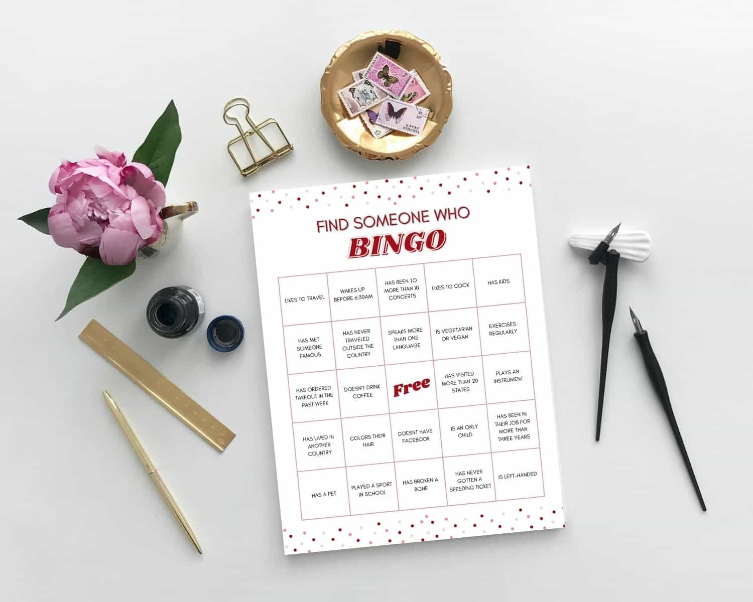Icebreaker Bingo sits on a desk next to some flowers and clips