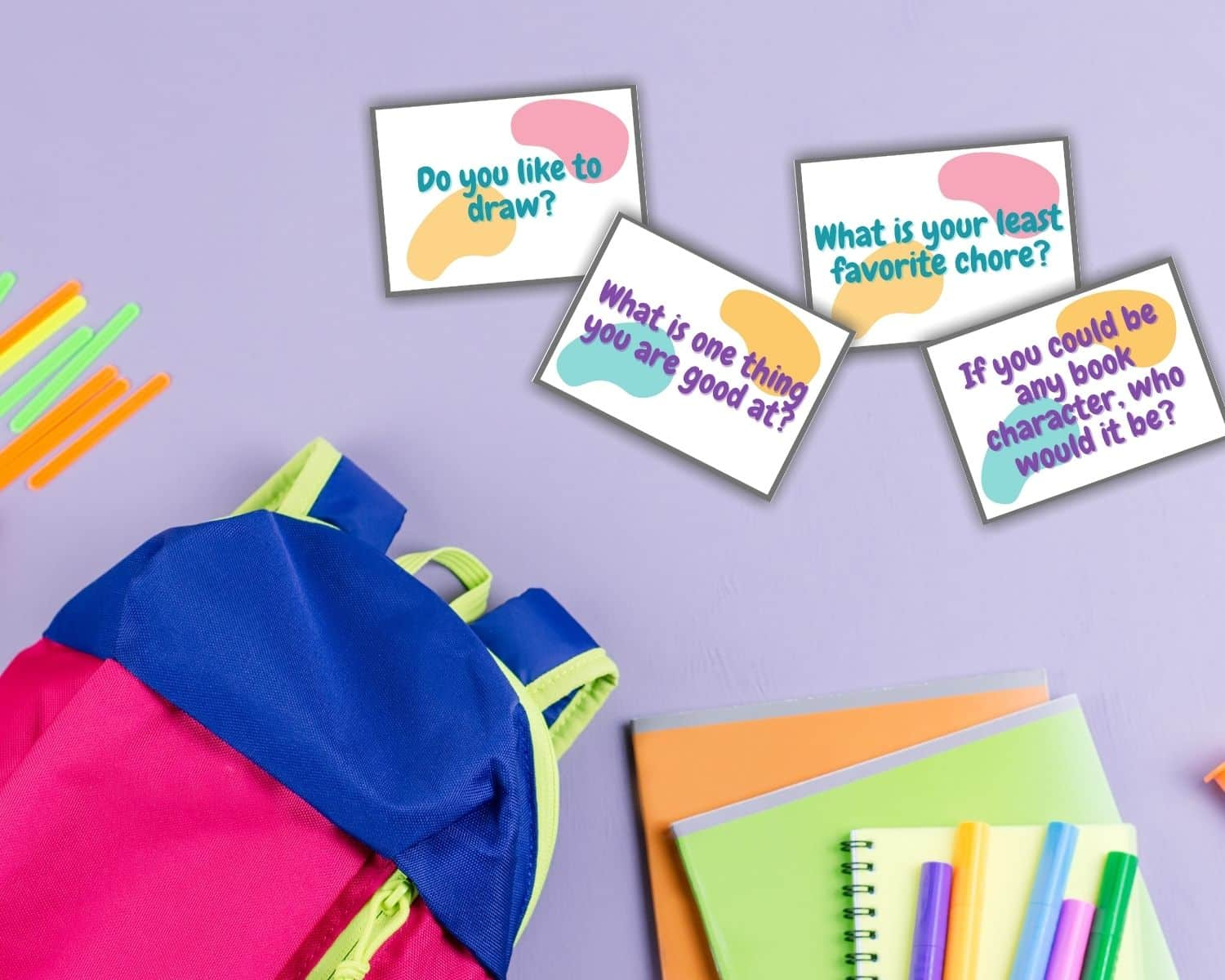 Kids conversation starters lay near a colorful backpack and notebooks