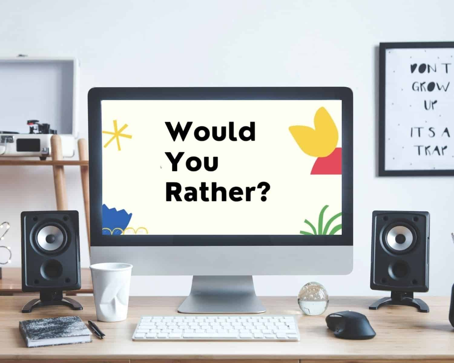 Would You Rather virtual game is shown on a computer sitting on a desk with an art print behind it