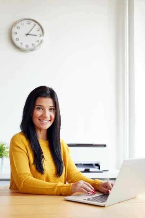 A woman wearing a yellow sweater sits in front of a computer