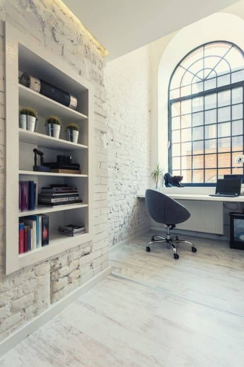 A white home office with a large window and a bookshelf build into the wall