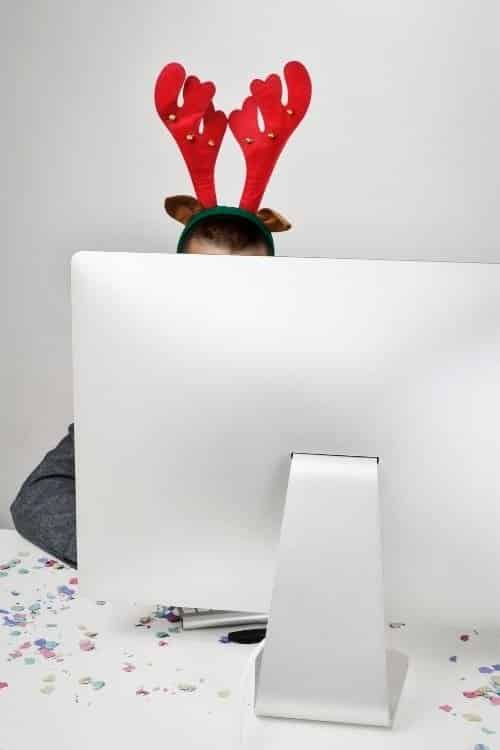 A man wearing reindeer ears sits behind a computer